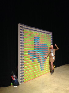 A woman gets her picture taken in front of a beer can creation at DellWorld