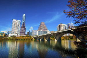 Austin downtown skyline with a bridge, Lady Bird / Town Lake, and an Autumn colored tree.