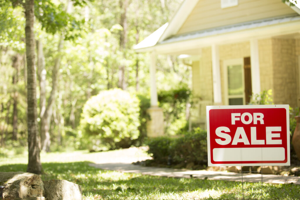 Home for sale with real estate sign in spring or summer season.